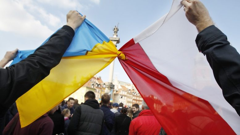 People hold tied  Polish, right,  and Ukrainian flags during a demonstration supporting  the  opposition  movement  in Ukraine,  in Warsaw, Poland, Sunday, Feb. 23, 2014. A top Ukrainian opposition figure assumed presidential powers Sunday, plunging Ukraine into new uncertainty after a deadly political standoff - and boosting long-jailed Yulia Tymoshenko's chances at a return to power. The whereabouts and legitimacy of President Viktor Yanukovych are unclear after he left the capital for his support base in eastern Ukraine.   (AP Photo/Czarek Sokolowski)